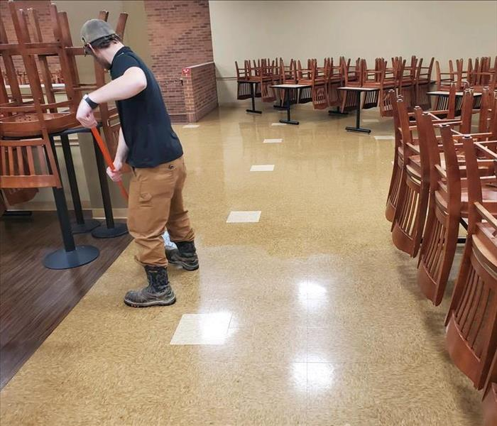 male staff member in black shirt mopping floor